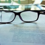 reading glasses on a typed manuscript page